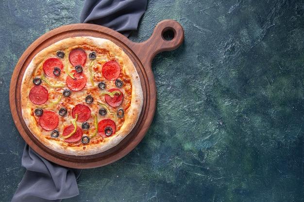 Saborosa pizza caseira em uma placa de madeira em uma toalha de cor escura em uma superfície escura isolada