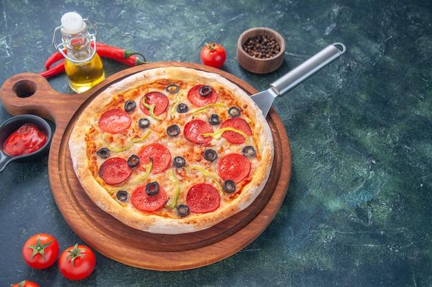 Saborosa pizza caseira na placa de madeira, garrafa de óleo, tomate pimenta na superfície escura