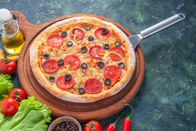 Saborosa pizza caseira na tábua de madeira, garrafa de óleo, tomate pimenta verde pacote na superfície escura