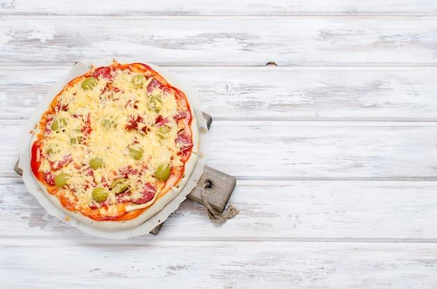 Saborosa pizza com especiarias e azeitonas em madeira branca
