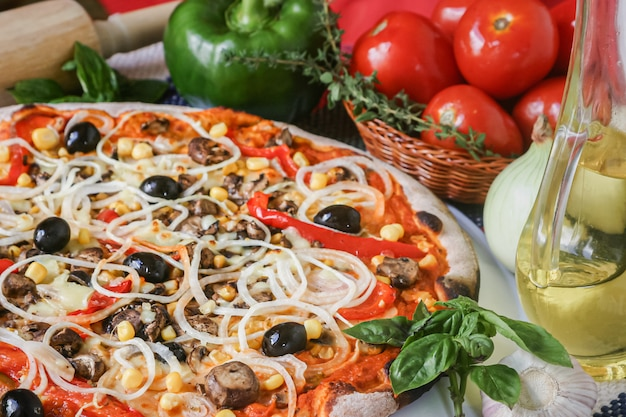 Saborosa pizza com queijo mussarela e legumes, cogumelos, pimentões, azeitonas, cebola, molho de tomate, especiarias e milho.