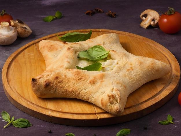 Saborosa pizza com queijo mussarela em forma de estrela em uma tábua de madeira