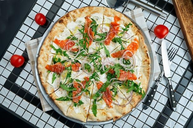 Saborosa pizza com queijo, tomate cereja, salmão, rúcula e parmesão em uma mesa de madeira. cozinha tradicional italiana. vista do topo. comida para o almoço