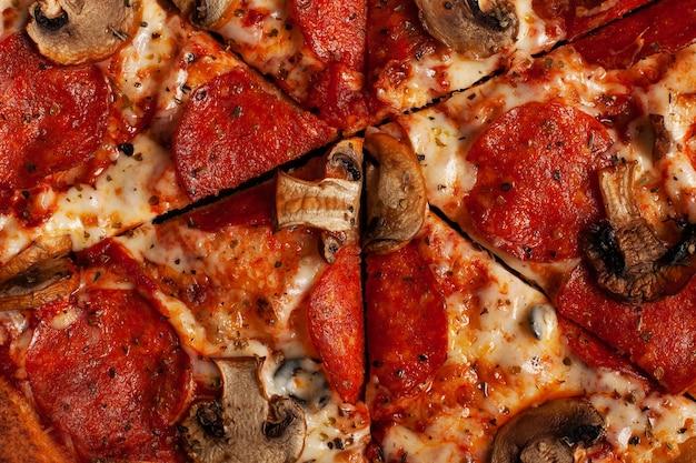 Saborosa pizza com salame e cogumelos. vista superior da pizza em fatias. fechar-se.