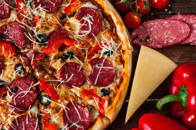 Saborosa pizza com salame servido na mesa de madeira
