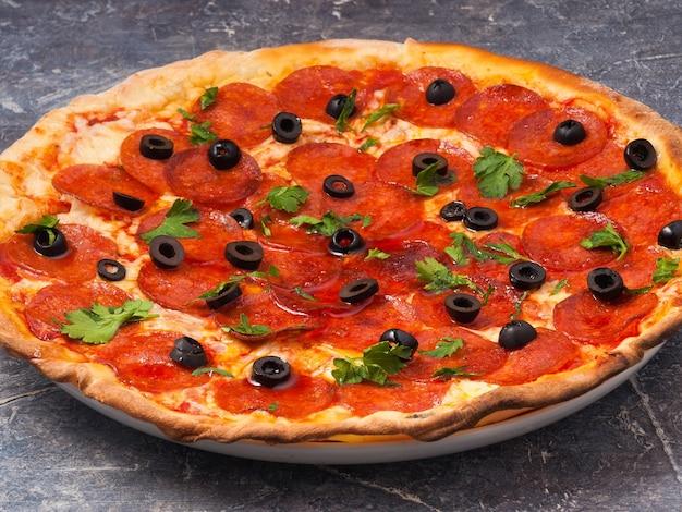 Saborosa pizza de calabresa com azeitonas e queijo muçarela decorada com verduras