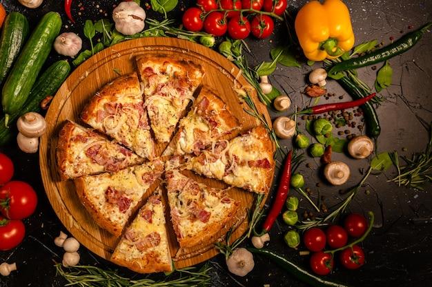 Saborosa pizza de calabresa e manjericão de tomate de ingredientes de cozinha em fundo preto de concreto. vista superior da pizza de pepperoni quente. com espaço de cópia para texto. postura plana. bandeira