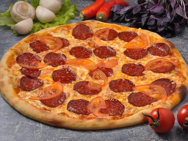 Saborosa pizza de calabresa em fundo cinza decorado com vegetais e cogumelos