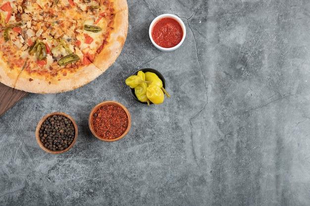 Saborosa pizza de frango na placa de madeira com vários condimentos.