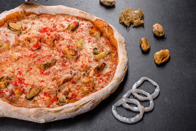 Saborosa pizza fatiada com frutos do mar e tomate em fundo preto. cozinha mediterrânea