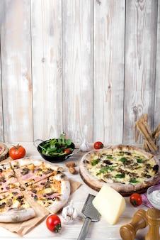 Saborosa pizza italiana com ingredientes frescos e utensílios em frente a parede de madeira