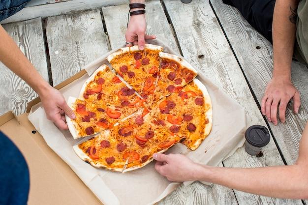 Saborosa pizza na caixa na superfície de madeira