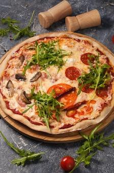 Saborosa pizza variada com diferentes recheios: salame, tomate, cogumelos, bacon, tomate seco. moldura vertical