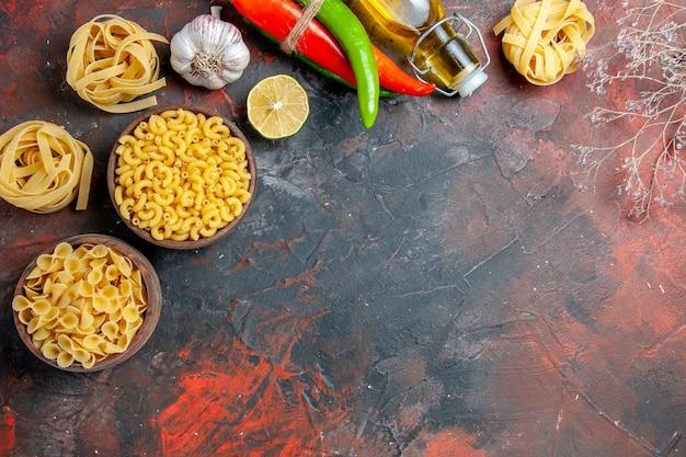 Saborosa preparação de jantar com massas não cozidas em várias formas e frasco de óleo de alho caído de alho limão em fundo de cor mista