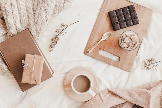 Saborosa refeição com bebida quente e livro na cama