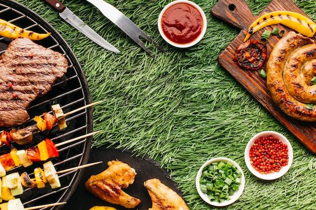 Saborosa refeição com carne grelhada e espeto de kebab no pano de fundo de grama