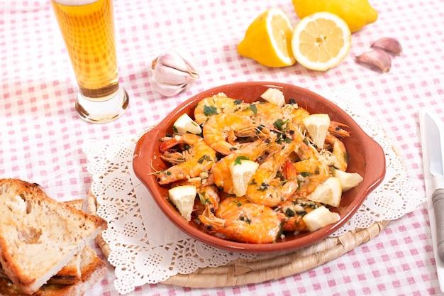 Saborosa refeição portuguesa com camarão frito, temperado com alho, azeite e salsa, servido com pão torrado.