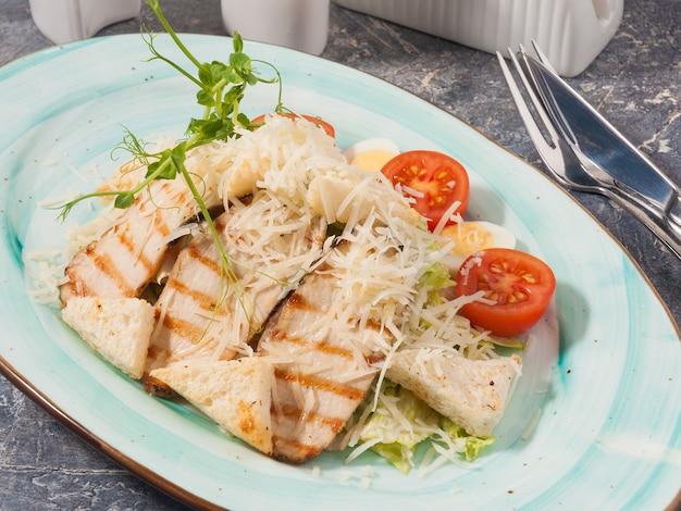 Saborosa salada caesar com frango em prato azul decorado com micro-verdes