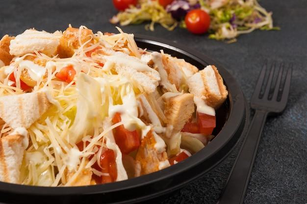 Saborosa salada caesar em uma tigela preta close-up