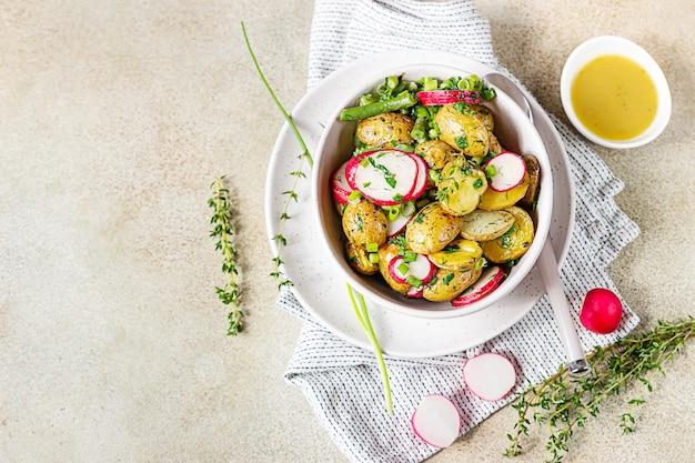 Saborosa salada de batata quente com feijão verde, rabanetes e ervas temperadas com azeite e molho de mostarda.