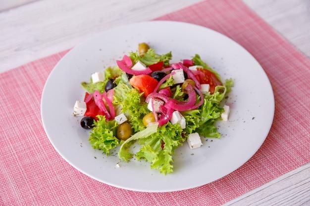 Saborosa salada grega fresca na mesa de madeira branca