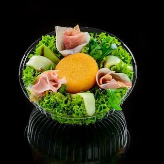 Saborosa salada mista com queijo camembert grelhado, presunto prosciutto, tomate orgânico e folhas verdes frescas. refeição dilicious saudável.
