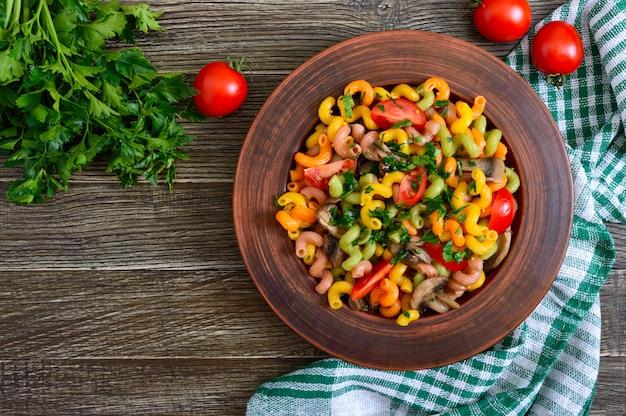 Saborosa salada quente. macarrão colorido com cogumelos e tomates frescos em uma tigela sobre uma mesa de madeira. macarrão colorido. a vista de cima