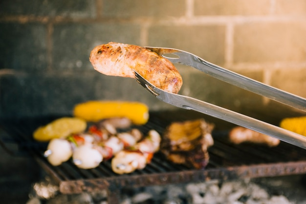 Saborosa salsicha grelhada em pinças de metal