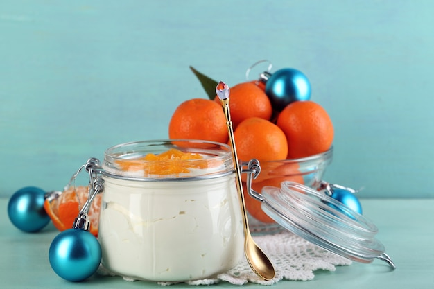 Saborosa sobremesa de leite com pedaços de tangerina fresca em jarra de vidro e bolas de natal