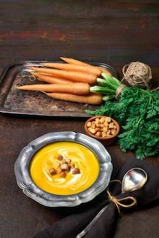 Saborosa sopa de cenoura vegetariana servida com croutons de creme em arco de metal estanho