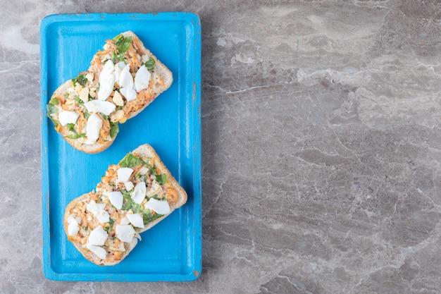 Saborosa torrada com vegetais fatiados na placa azul.