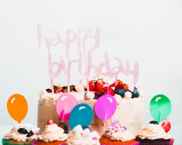 Saborosa torta fresca com frutas e feliz aniversário título perto de conjunto de muffins