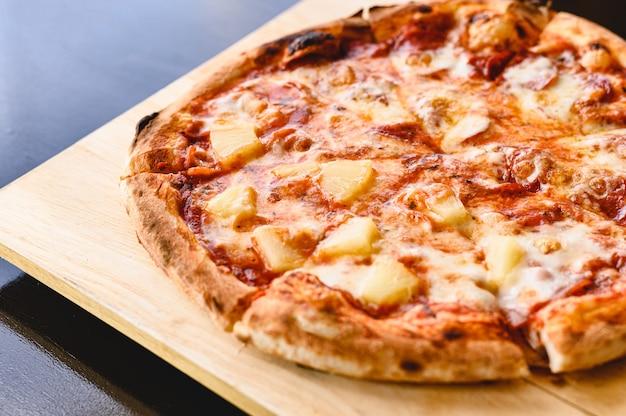 Saborosa tradição de torta de pizza havaiana e salame cozinhando ingredientes bacon e tomates em mesa preta em restaurante original