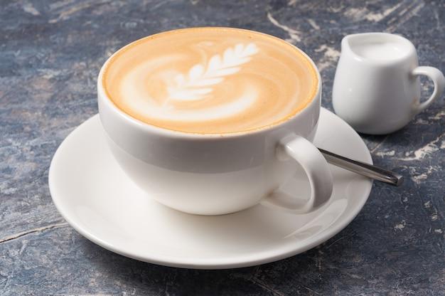 Saborosa xícara grande de cappuccino em um fundo cinza