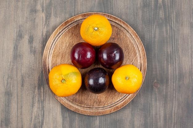 Saborosas ameixas com deliciosas tangerinas num prato de madeira. foto de alta qualidade