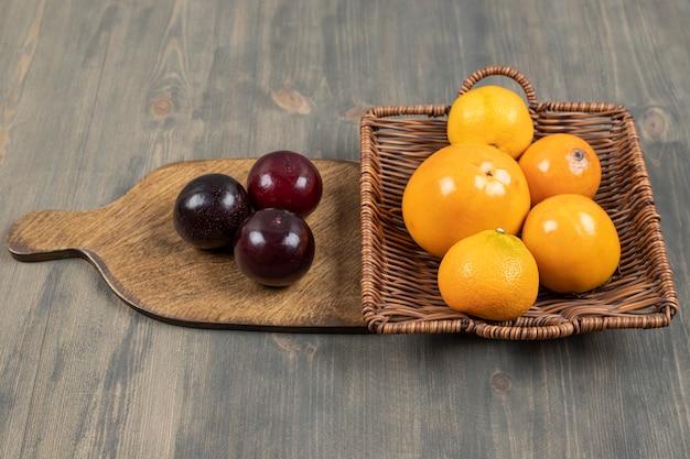 Saborosas ameixas com deliciosas tangerinas num prato de madeira