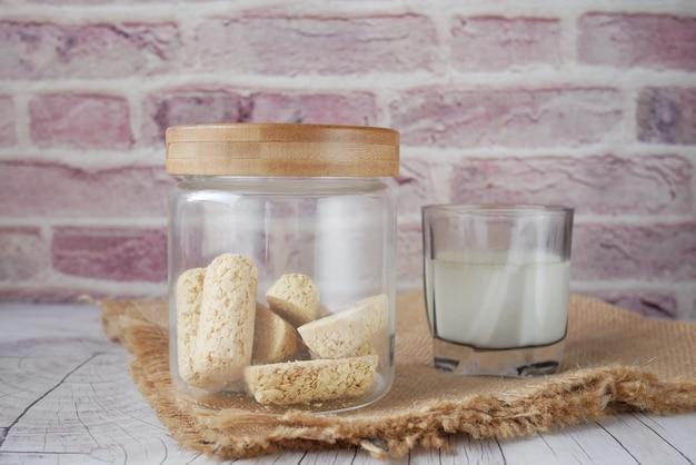 Saborosas barras de aveia em frasco de vidro e leite na mesa