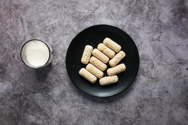 Saborosas barras de aveia em um prato e copo de leite na mesa
