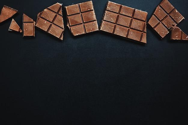 Saborosas barras de chocolate em fundo escuro. vista de cima. fundo de chocolate.