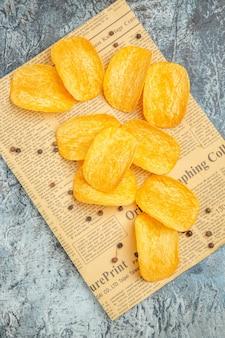 Saborosas batatas fritas caseiras e pimenta no jornal em fundo cinza