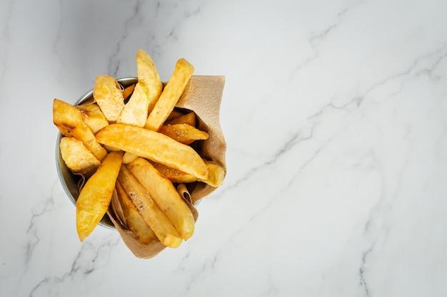 Saborosas batatas fritas em fundo de mármore