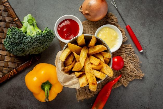 Saborosas batatas fritas em fundo escuro