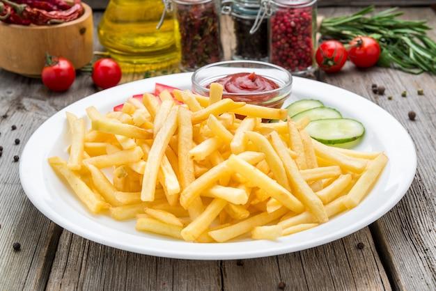 Saborosas batatas fritas na mesa de madeira