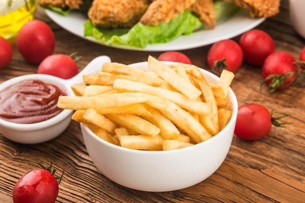 Saborosas batatas fritas na tábua, na superfície da mesa de madeira