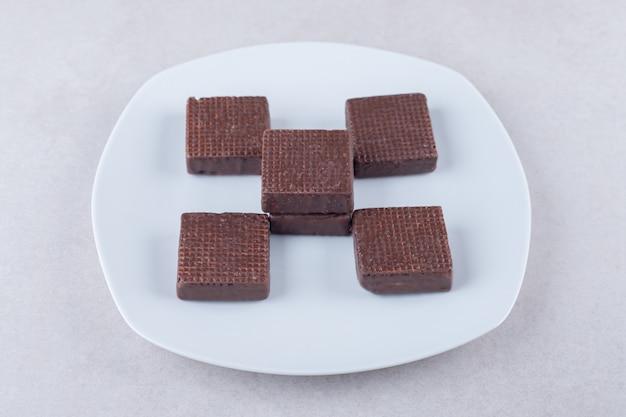 Saborosas bolachas revestidas de chocolate num prato na mesa de mármore.