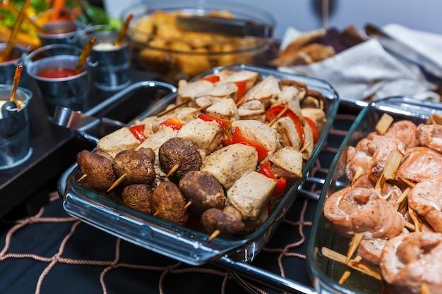 Saborosas carnes assadas variadas com vegetais grelhados para um bufê de festa