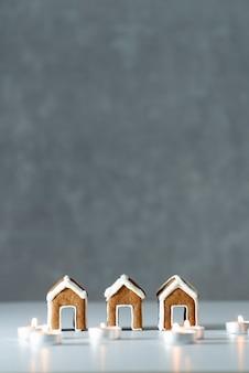Saborosas casas de pão de gengibre pintadas com vidros e velas em fundo cinza. quadro vertical. copie o espaço