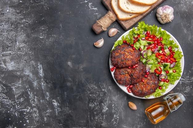 Saborosas costeletas de carne com salada de legumes em prato cinza de mesa refeição de comida