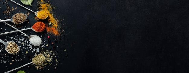 Saborosas especiarias coloridas em colheres em fundo escuro. vista do topo