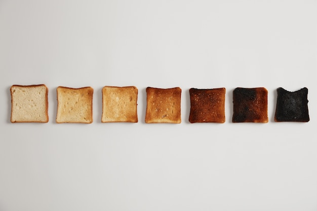 Saborosas fatias de pão torrado, do não torrado ao queimado. estágios de torrada. foco seletivo. lanche delicioso crocante. superfície branca. conjunto de torradas, cada uma torrada por mais tempo, grau de torra.